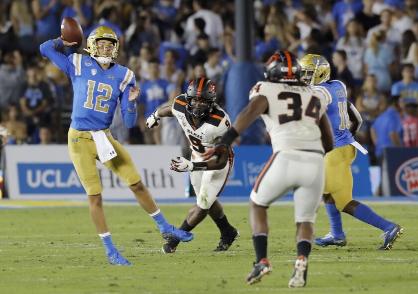 UCLA quarterback Austin Burton (12) runs out of the pocket against Oregon State during the first half Saturday at the Rose Bowl.