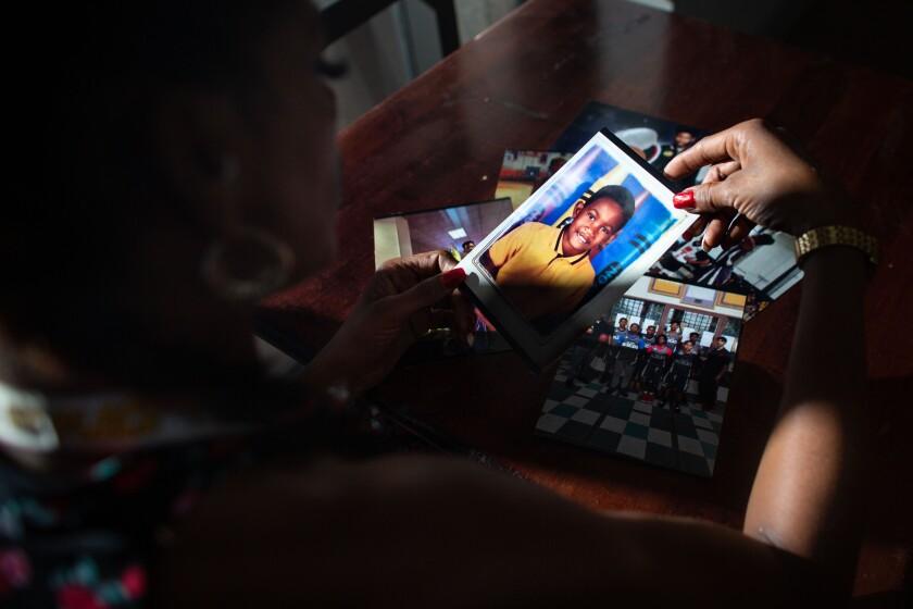 Taloma Miller looks through a stack of photos of her late son Semaj.