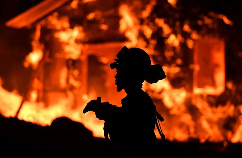An inmate firefighter monitors flames as a house burns in the Napa wine region.