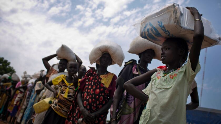 In this photo taken Oct. 19, 2016, a young girl who fled fighting in Leer, South Sudan, joins the queue for food aid being distributed by the World Food Program in Bentiu.
