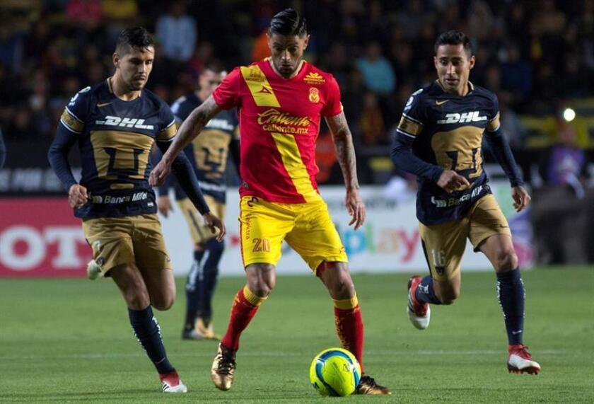 El jugador Rodrigo Millar (c) de Morelia disputa el balón con David Cabrera (i) y Luis Fuentes (d) de Pumas. EFE/Archivo