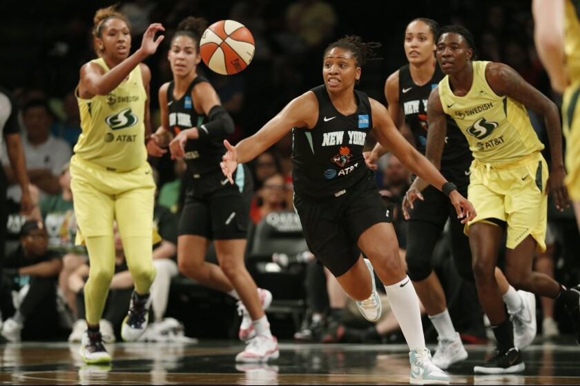 FILE - In this Aug. 11, 2019, file photo, New York Liberty guard Tanisha Wright, center, goes after a loose ball during the first half of the team's WNBA basketball game against the Seattle Storm at Barclays Center in New York. The Atlanta Dream hired longtime WNBA player Tanisha Wright as its new head coach on Tuesday, Oct. 12, 2021, looking to bring stability to a team that struggled under two interim coaches this past season. The 37-year-old Wright played 14 seasons with the Seattle Storm, New York Liberty and Minnesota Lynx. (AP Photo/Kathy Willens, File)