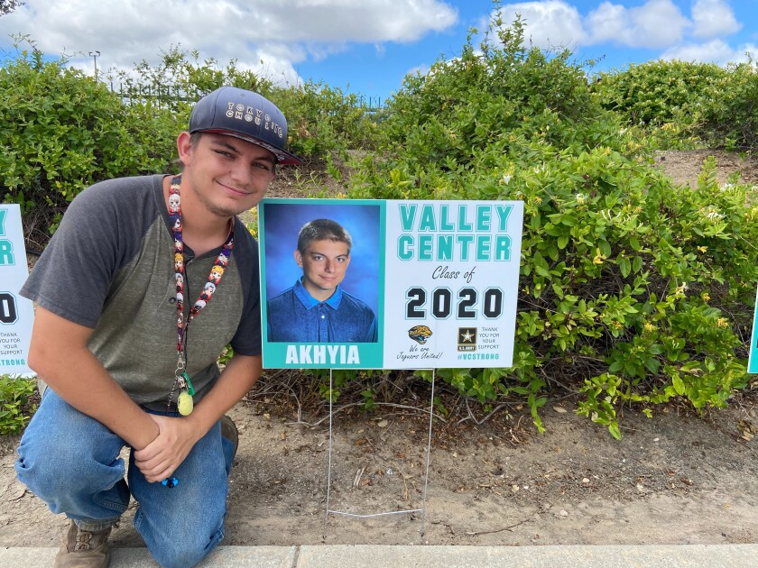 Senior Akhyia Avila-Deuel poses next to his personalized photo sign, posted at Valley Center High School.