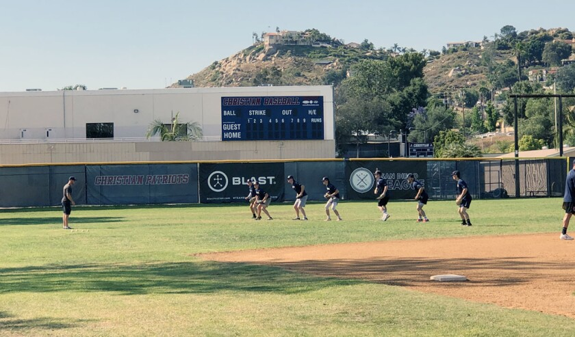 A San Diego League coach puts players through a drill in the outfield at Christian High during Wednesday's practice.