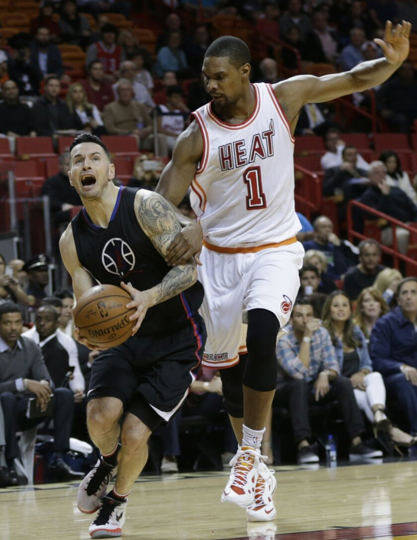 Los Angeles Clippers guard J.J. Redick, left, is fouled by Miami Heat forward Chris Bosh during the first half of an NBA basketball game, Sunday, Feb. 7, 2016, in Miami. (AP Photo/Lynne Sladky)