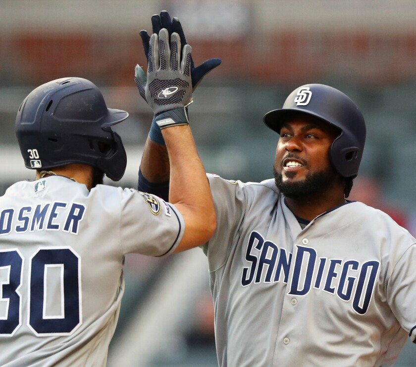 Franmil Reyes, right, gets a high-five from Eric Hosmer after hitting the first of his two home runs against the Atlanta Braves on Tuesday. Hosmer would also homer in the sixth inning.