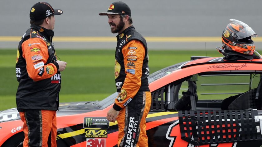 Martin Truex Jr., right, talks with a crew member during a rain delay in the NASCAR Clash auto race