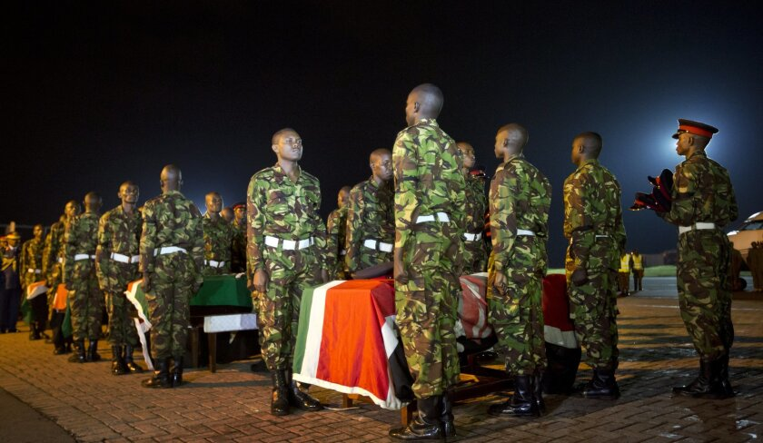 FILE - In this Monday, Jan. 18, 2016 file photo, military pallbearers stand to attention next to the coffins of four Kenyan soldiers who were killed in Somalia, at a ceremony to receive their bodies which were airlifted to Wilson Airport in Nairobi, Kenya. Somalia's president Hassan Sheikh Mohamud said Wednesday, Feb. 24, 2016 that at least 180 Kenyan soldiers were killed in Somalia in an extremist attack on their base in January by al-Qaida affiliate al-Shabab. (AP Photo/Ben Curtis, File)