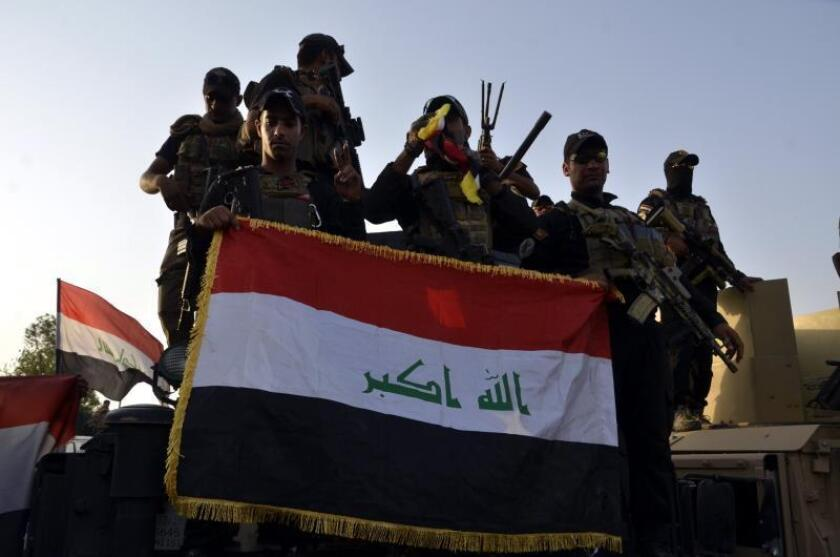 Iraqi soldiers hold up the Iraqi national flag in central Mosul, northern Iraq, 10 July 2017 (reissued 09 December 2017). EFE
