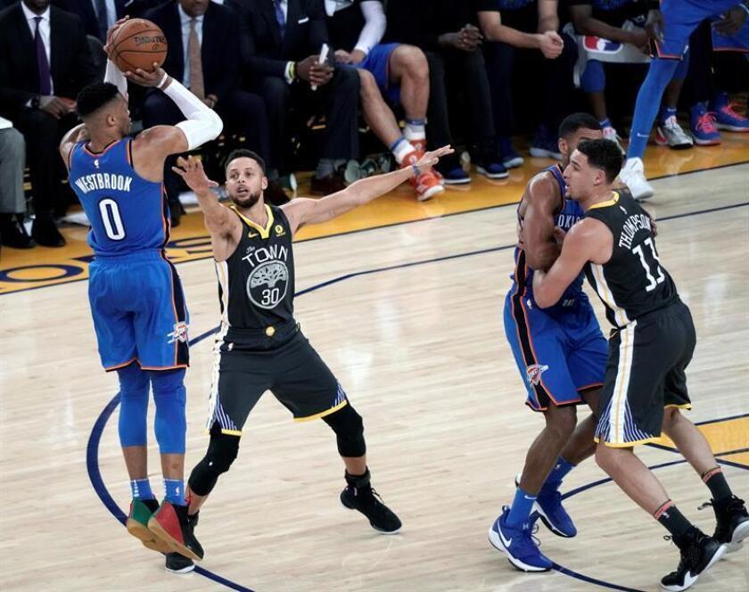 El jugador de los Warriors de Golden State Stephen Curry (2i) lucha por el balón con Russell Westbrook (i) de los Thunder de Oklahoma City durante el partido de la NBA entre los Thunder de Oklahoma City y los Warriors de Golden State en el Oracle Arena en Oakland (Estados Unidos) este 6 de febrero de 2018. EFE