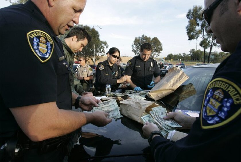 San Diego police Officers Michael Pridemore (left) and Jeff Wuehler (far right) counted the amount of money found yesterday along Interstate 805 after cash was tossed out a car window during a pursuit.(Peggy Peattie / Union-Tribune)