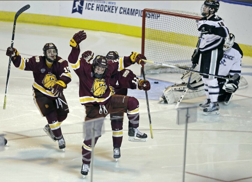 Minnesota-Duluth wing Karson Kuhlman (20) celebrates his winning goal with teammates Willie Raskob, left, and Austin Farley, right, as Providence defenseman Anthony Florentino (16) and goalie Nick Ellis (35) react in the second overtime period of a regional semifinal game in the NCAA college hockey tournament, Friday, March 25, 2016, in Worcester, Mass. Minnesota-Duluth won 2-1. (AP Photo/Elise Amendola)