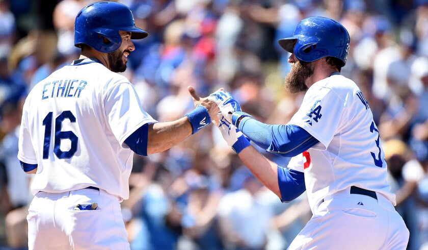 Dodgers left fielder Scott Van Slyke is congratulated by left fielder Andre Ethier after hitting a two-run home run against the Rockies in the sixth inning Sunday.