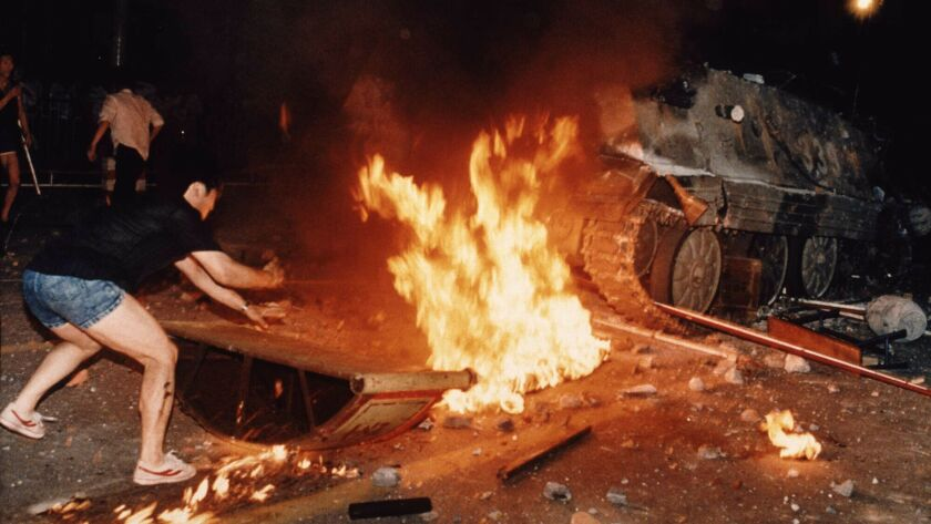 On June 4, 1989, a Chinese protester tried to block an already burning armored personnel carrier that rammed through protest lines during an army attack on anti-government demonstrators. A soldier who escaped the armored vehicle was killed by demonstrators.