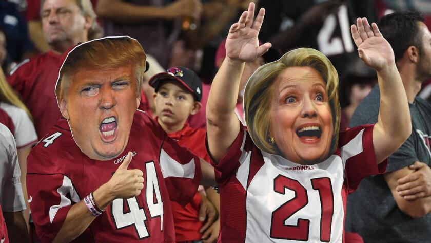 Aficionados de los Cardenales de Arizona con máscaras de Donald Trump y Hillary Clinton. (Norm Hall / Getty Images)