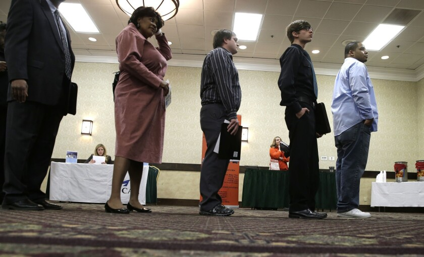 Job seekers line up to meet a prospective employer at a career fair at a hotel in Dallas.