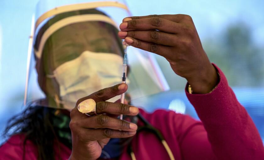 Health worker preparing dose of COVID-19 vaccine