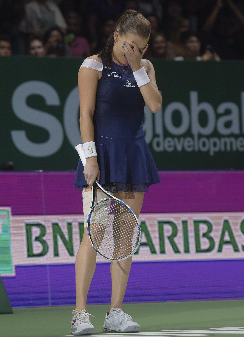 Agnieszka Radwanska of Poland reacts as she beats Petra Kvitova of the Czech Republic to win the singles final at the WTA tennis finals in Singapore Sunday, Nov. 1, 2015. (AP Photo/Joseph Nair)