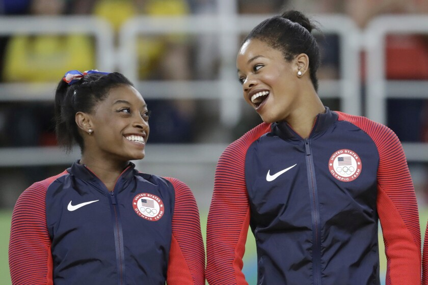 FILE - In this Aug. 9, 2016, file photo, U.S. gymnasts and gold medallists, Simone Biles, left and Gabrielle Douglas celebrate on the podium during the medal ceremony for the artistic gymnastics women's team at the 2016 Summer Olympics in Rio de Janeiro, Brazil. The success of Olympic gymnastics champions Gabby Douglas and Simone Biles has created a spike in interest in the sport in Black communities. Representation among Black girls at the upper reaches of women's gymnastics is rising. Half of the U.S. Olympic team in Tokyo are women of color. (AP Photo/Julio Cortez, File)