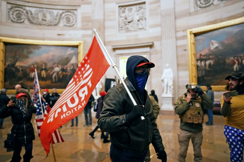 """A masked protester carries a red flag that says """"Trump Nation"""" in the Rotunda of the U.S. Capitol."""