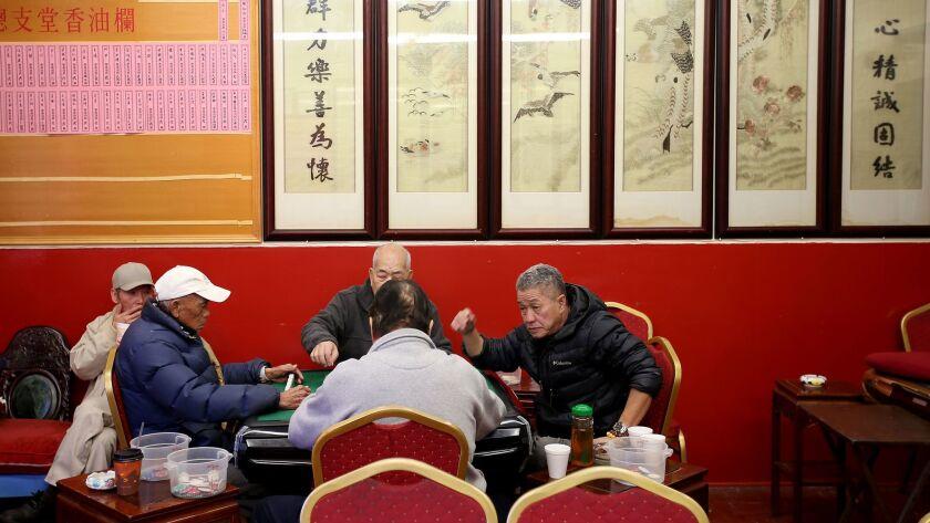 A group pf men play mah jong at the Hop Sing Tong.