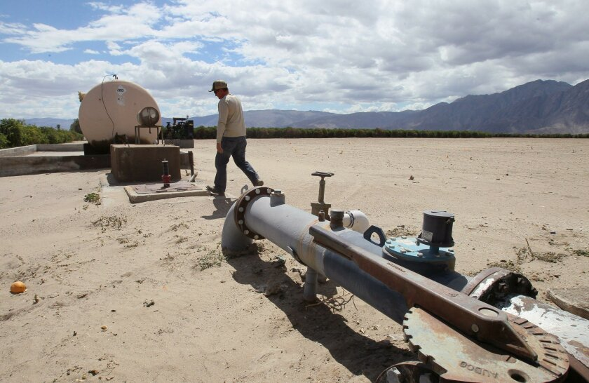 Seley Ranch manager Ryan Fancy walks past a pipeline that carries water pumped from one of the ranch's wells in Borrego Springs.