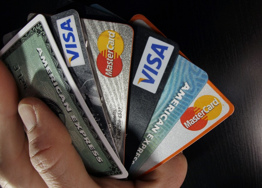 A hand holding credit cards.