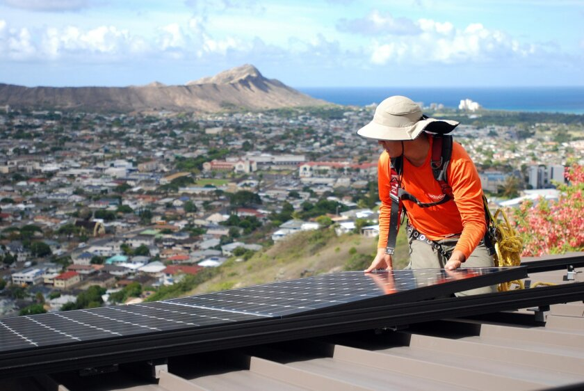 In this Friday, July 8, 2016, photo, Dane Hew Len, lead installer for RevoluSun, places a solar panel on a roof in Honolulu. Hawaii is a national leader in rooftop solar power, and the state has an ambitious goal of using only renewable energy by 2045. But people are being shut out of solar incentive programs because of limits set by the state. (AP Photo/Cathy Bussewitz)