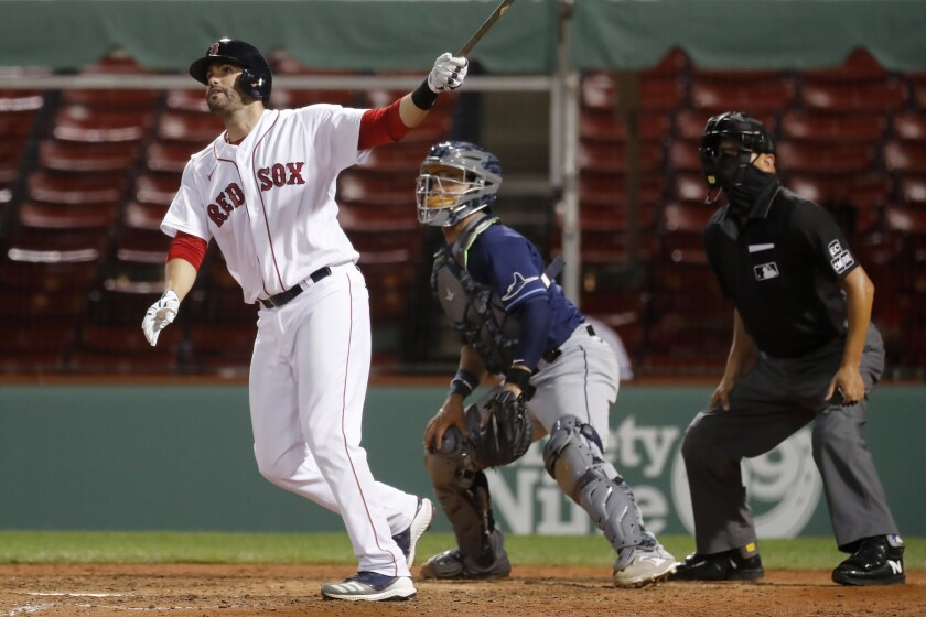 Boston Red Sox's J.D. Martinez, left, follows through on his grand slam in front of Tampa Bay Rays' Michael Perez during the eighth inning of a baseball game, Wednesday, Aug. 12, 2020, in Boston. (AP Photo/Michael Dwyer)