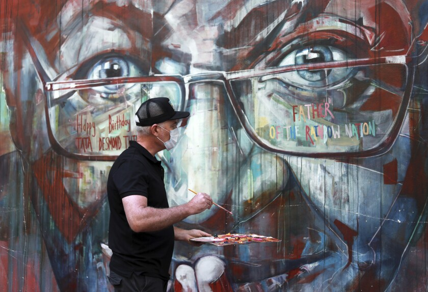 A wall mural, depicting Anglican Archbishop Emeritus, Desmond Tutu, is restored by the artist Brian Rolfe after it was defaced, in Cape Town, South Africa Thursday Oct. 7, 2021. As South Africa's anti-apartheid icon, Tutu turns 90, recent racist graffiti on the wall mural portrait highlights the continuing relevance of his work for equality. (AP Photo/Nardus Engelbrecht)