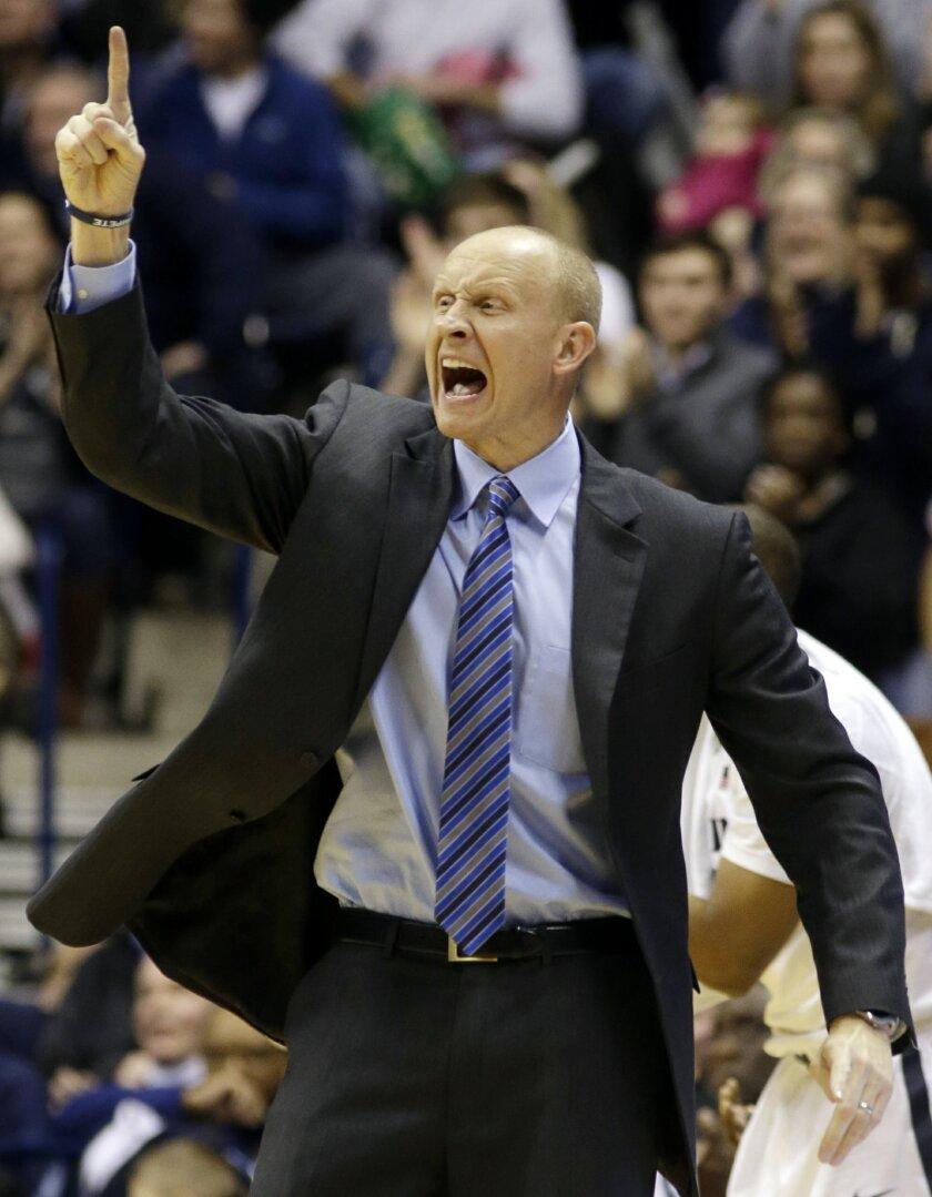 Xavier head coach Chris Mack calls a play in the second half of an NCAA college basketball game against Butler, Saturday, Jan. 4, 2014, in Cincinnati. Xavier won 79-68. (AP Photo/Al Behrman)