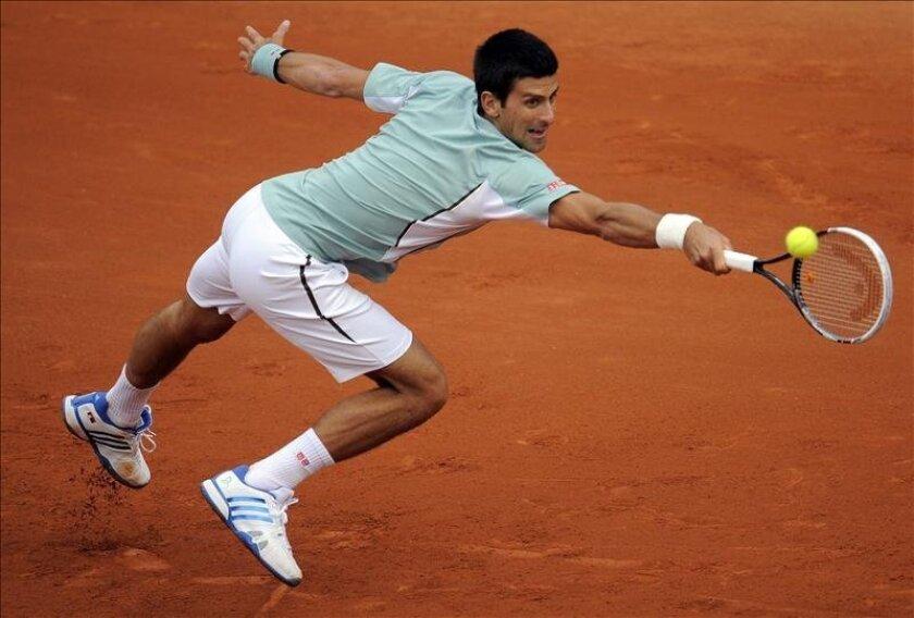 El tenista serbio Novak Djokovic devuelve la bola durante el partido del torneo de primera ronda del torneo de Roland Garros que disputó contra el belga David Goffin en París, Francia. EFE