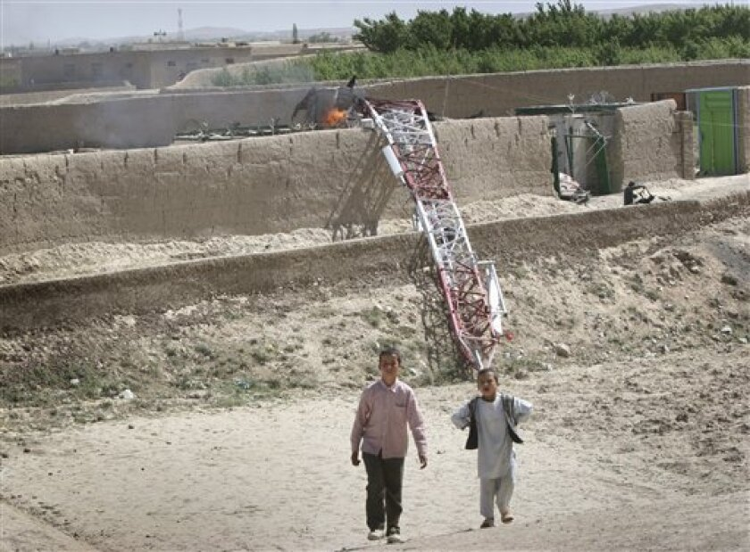 Afghan children walk past a damaged communication mast belonging to Emirates Telecommunication Corporation (Etisalat) after it was burnt and destroyed by Taliban militants in Ghazni, west of Kabul, Afghanistan on Wednesday, June 1, 2011. (AP Photo/Rahmatullah Nikzad)