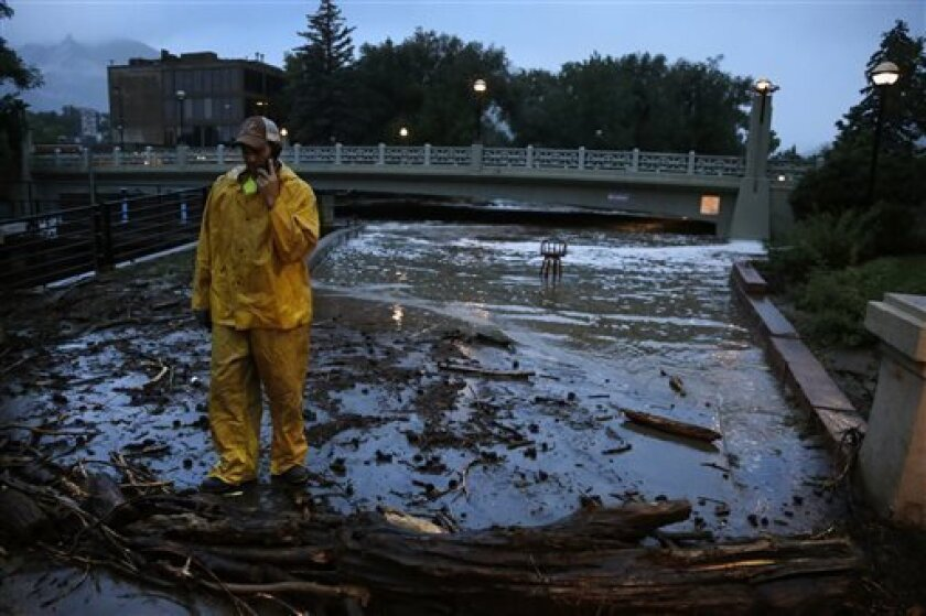 A city worker talks on his phone while surveying high water levels on Boulder Creek following overnight flash flooding in downtown Boulder, Colo., Thursday, Sept 12, 2013. Flash flooding in Colorado has left two people dead and the widespread high waters are keeping search and rescue teams from rea