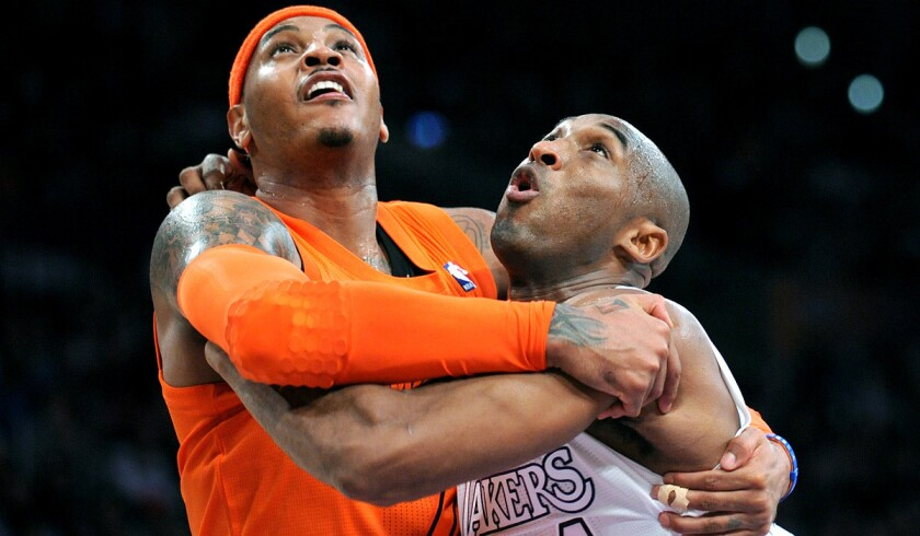 Carmelo Anthony, then with the New York Knicks, and Kobe Bryant jump with their arms around each other as they fight for position in a 2014 game.