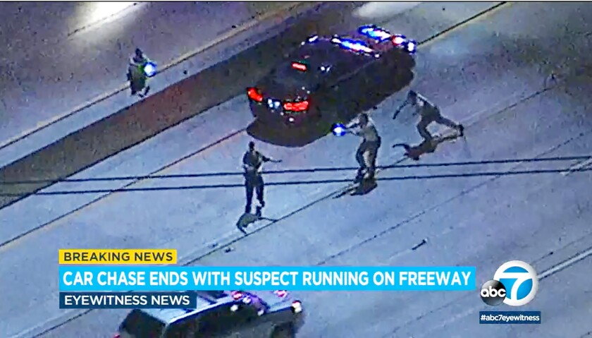 This image taken from video provided by KABC-TV shows a man, lower left, who had been pursued by Los Angeles County Sheriff's deputies, finally being taken down on the Interstate 5 freeway in the Newhall Pass area of Los Angeles late Thursday evening, March 5, 2020. Deputies shot the suspect in the leg after he led them on a pursuit and fired at officers and a police helicopter before running across the freeway, authorities said Friday. The suspect, who was not identified, was in stable condition with a single gunshot wound, according to the Sheriff's Department. The suspect's passenger was also taken into custody. (KABC-TV via AP)