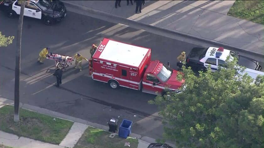 A person is wheeled into an ambulance after a shooting near Crenshaw High School on Jan. 31.