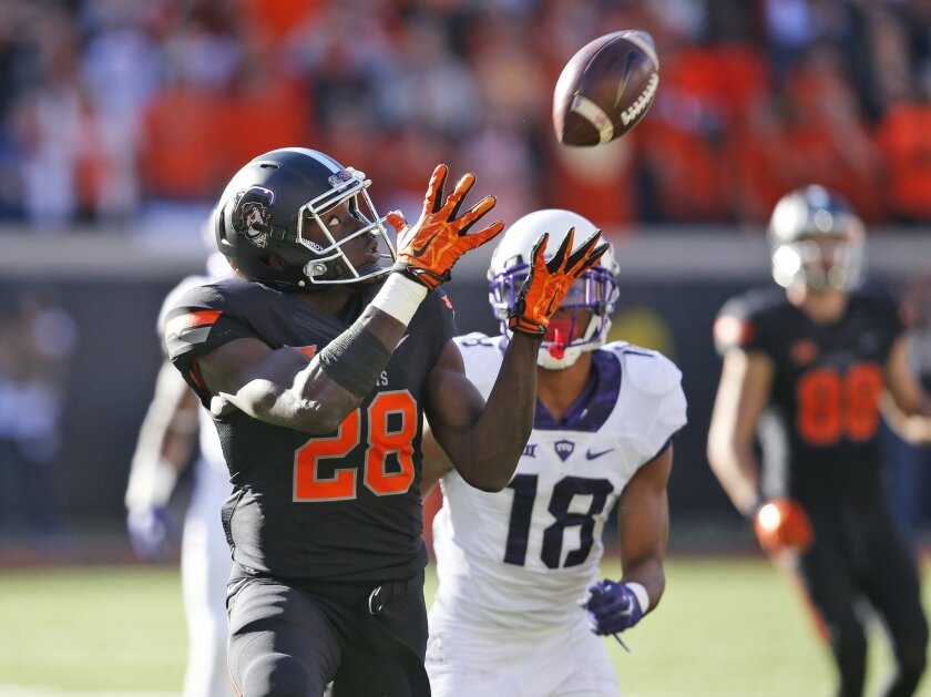 Oklahoma State wide receiver James Washington (28) catches a pass in front of TCU safety Nick Orr (18) and carries it in for a touchdown in the first quarter of an NCAA college football game in Stillwater, Okla., Saturday, Nov. 7, 2015. (AP Photo/Sue Ogrocki)