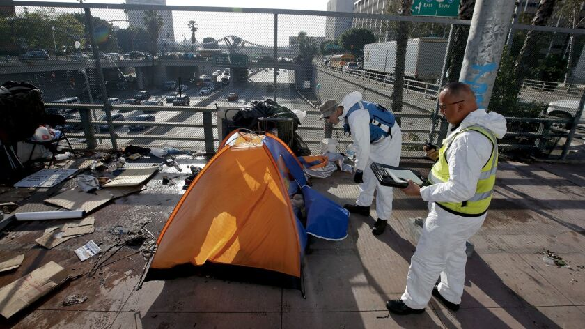 Sanitation and hazmat crews clear out homeless tents on the Main Street overpass above the 101 Freeway on March 15, 2016.