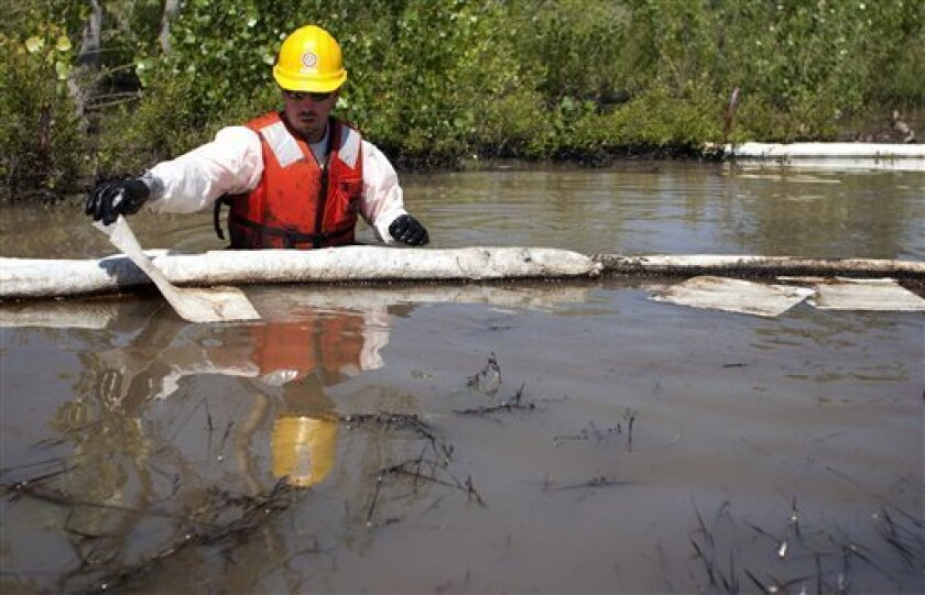 Cleanup workers use oil absorbent materials along side the Yellowstone River in Laurel, Mont., Wednesday July 6, 2011. An ExxonMobil pipeline near Laurel ruptured and spilled an estimated 1,000 barrels of crude into the Yellowstone. (AP Photo/Jim Urquhart)