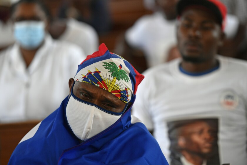 A person cries during a memorial service for assassinated President Jovenel Moïse in the Cathedral of Cap-Haitien, Haiti, Thursday, July 22, 2021. Moïse was killed in his home on July 7. (AP Photo/Matias Delacroix)