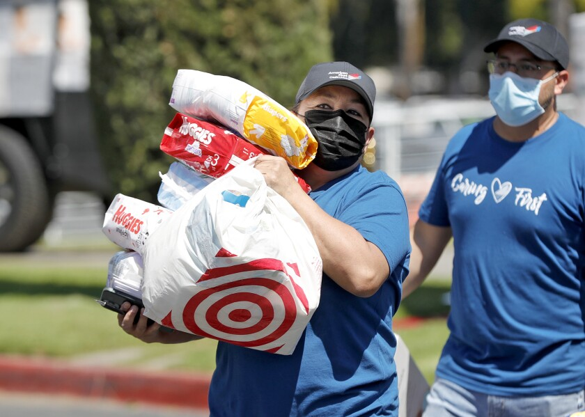 Volunteer groups unload diapers at the Christ Cathedral Church in Garden Grove on Friday.