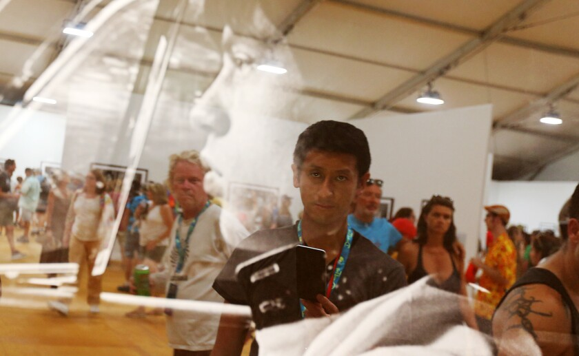 """Terayuki Kobayashi, 25, who came from Yokohama, Japan, examines a photo of Rolling Stones lead singer Mick Jagger in an exhibit at the Desert Trip mega-concert. Kobayashi came to Indio because he said his city is """"too small"""" for most of the festival's rock stars to visit."""