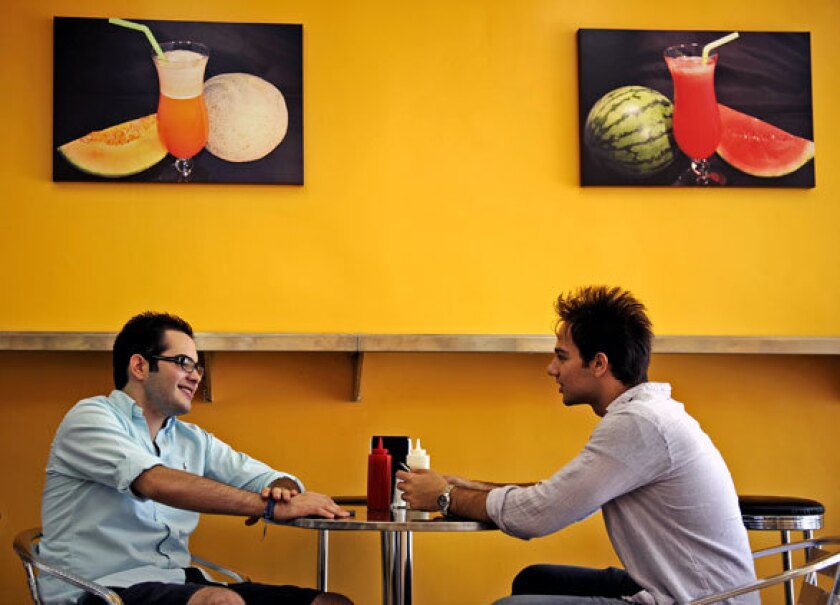 College students chat as they wait for their Persian pizza during lunch in Westwood.