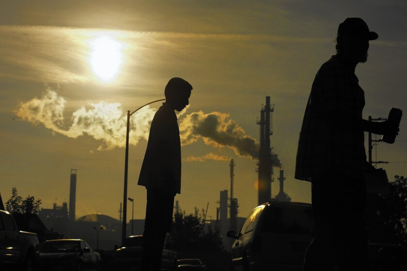 Jesse Ceja and his grandfather, Paulo Torres, 69, stand on Emden Street in Wilmington, where they live next to the Phillips 66 refinery seen in the background.