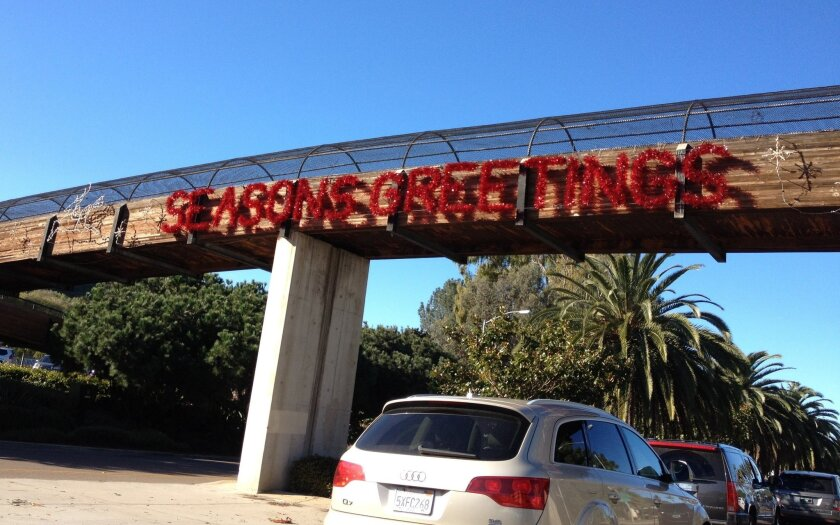 The traditional Seasons Greetings sign on the Torrey Pines Road pedestrian bridge was conspicuously absent this year before La Jolla Town Council trustees Ramin Pourteymour and Egon Kafka came forward with the cash for its installation. Daniel Lew photos