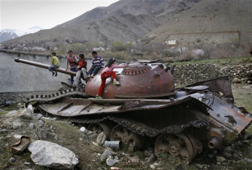 In this Saturday, March 26, 2011 photo, Afghan children play on a destroyed Soviet - made armored tank in Panjshir north of Kabul, Afghanistan. (AP Photo/Ahmad Nazar)