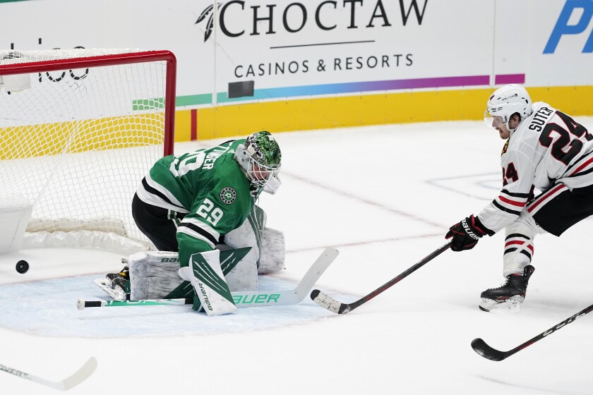 Dallas Stars goaltender Jake Oettinger (29) is unable to stop a shot by Chicago Blackhawks' Pius Suter (24) in overtime of an NHL hockey game in Dallas, Tuesday, Feb. 9, 2021. The Blackhawks won 2-1. (AP Photo/Tony Gutierrez)