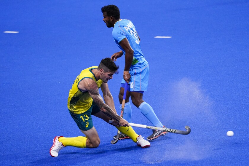 Australia's Blake Govers (13) passes against India's Amit Rohidas (30) during a men's field hockey match at the 2020 Summer Olympics, Sunday, July 25, 2021, in Tokyo, Japan. (AP Photo/John Minchillo)