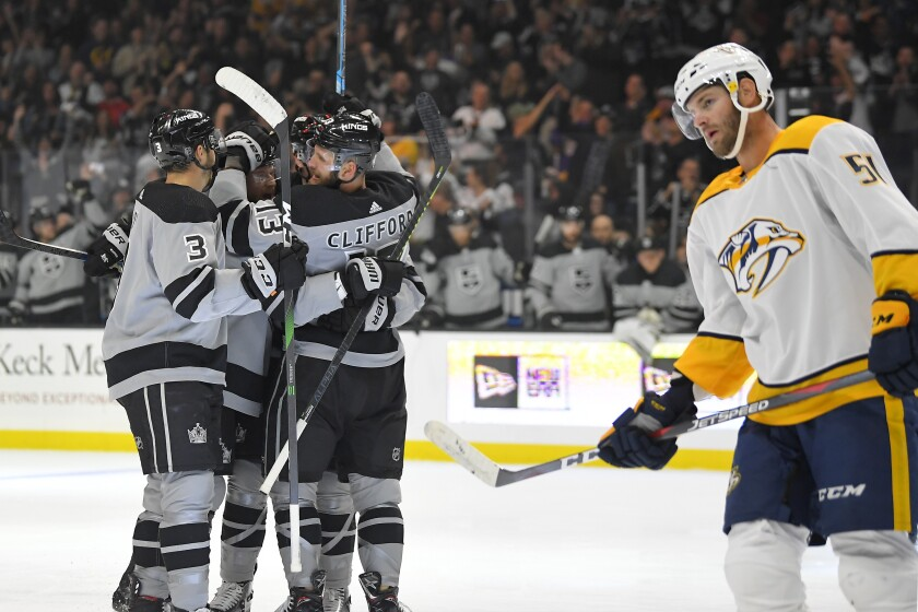 Los Angeles Kings left wing Kyle Clifford, back right, celebrates his goal with defenseman Matt Roy, left, and another teammate, as Nashville Predators left wing Austin Watson skates by during the second period of an NHL hockey game Saturday, Oct. 12, 2019, in Los Angeles. (AP Photo/Mark J. Terrill)